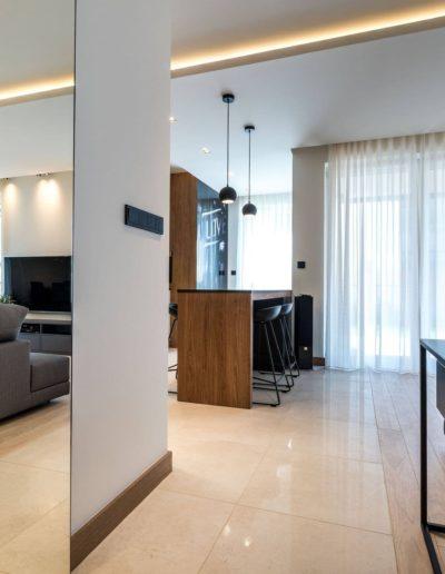 3-5-Format-Design-projekt-apartamentu-w-Poznaniu-wejście-do-salonu-aneks-kuchenny-drzwi-przesuwne-z-lustrem