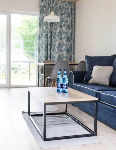 9-10-Format-Design-projekt-domu-letniskowego-salon-podłoga-bielona-aranżacja-okien-ława-wypoczynek